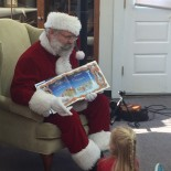 Santa reading a book to a child.